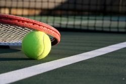 Tennis ball and racket next to the net